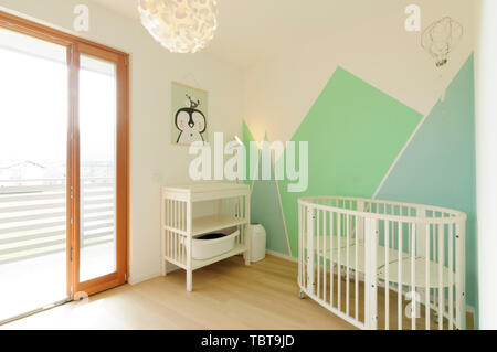 Home interior: bright Scandinavian style nursery with wooden floor and walls painted with geometric shapes in pastel colors - Stock Photo