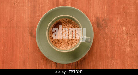 A panorama of a cup of black coffee on a dark rustic wooden background, shot from above with copy space, toned image - Stock Photo