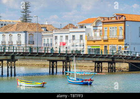 Pedestrian bridge over River Gilao and wooden boats. Old town of Tavira, Algarve, Portugal - Stock Photo