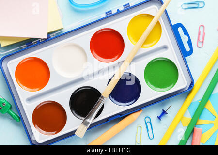 Set of watercolor paints in a box with paintbrush and stationery supplies. Kids creation concept. - Stock Photo