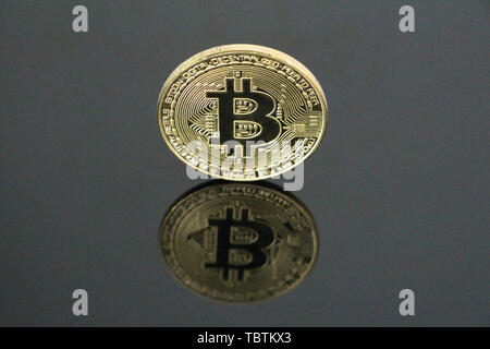 One gold coin bitcoin on a black background. Bitcoin is on its side. One can see his reflection. Cryptocurrency concept gold bitcoin. No people, empty - Stock Photo
