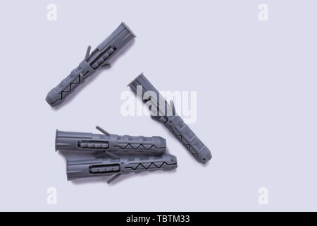Plastic dowels isolated on white background. Four grey plastic dowels. Space for text. - Stock Photo