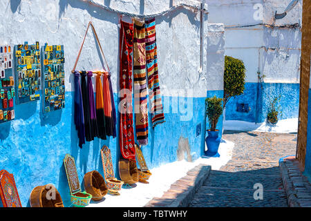 Blue and white traditional street in Medina in Rabat. On the wall hang carpets and magnets for sale Morocco, Africa - Stock Photo