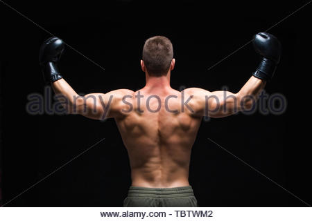 Powerful back. Muscular young man in black boxing gloves and shorts shows the different movements and strikes in the studio on a dark background. Stro - Stock Photo