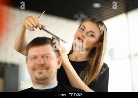 Female Hairdresser Combing Male Client in Salon. Woman Hairstylist Making Hairstyle for Man Sitting in Beauty Studio. Stylist Holding Comb and Scissor - Stock Photo