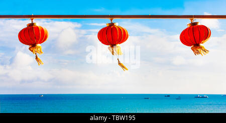 Red Chinese Paper Lanterns against a Blue Sky and sea - Stock Photo