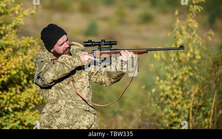 Regulation of hunting. Hunter hold rifle. Bearded hunter spend leisure hunting. Focus and concentration of experienced hunter. Hunting masculine hobby concept. Man brutal gamekeeper nature background. - Stock Photo
