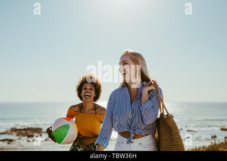 Cheerful young women walking with a ball and bag along the sea shore. Female friends on beach vacation.