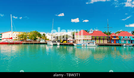 St johns, Antigua - March 05, 2016: quay with houses and yachts in turquoise sea on blue sky. Travelling and wanderlust. Summer vacation on tropical island. - Stock Photo
