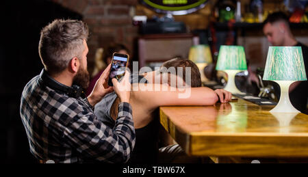 Hipster taking photo drunk friend. Drunk friends in bar. Fall asleep at bar counter. Take photo to remember party. Hipster making fun of drunk friend. Man drunk fall asleep and guy with smartphone. - Stock Photo