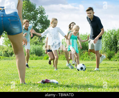 Mother and father with kids playfully running after ball outdoors on green lawn in park. Focus on boy - Stock Photo