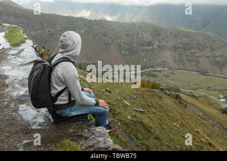 Young tourist man with backpack sits on a slope against the background of the Caucasus Mountains, Georgia on a foggy day - Stock Photo