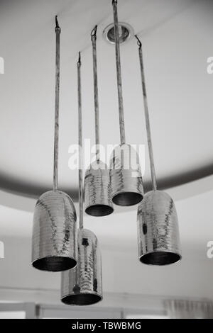 A group of mettalic hanging lights on white ceiling in loft designed appartment. Interior design concept. - Stock Photo