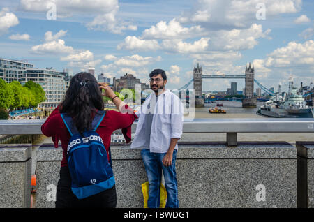 A lady takes a photography of her male companion on London Bridge with The River Thames, HMS Belfast and Tower Bridge in the background.