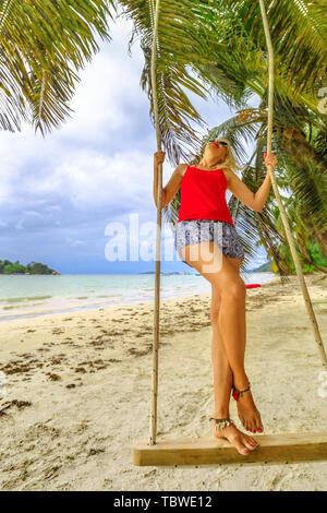 Happy tourist woman swinging on tropical beach under coconut palm trees of Anse Volbert Cote d'Or, Praslin, Seychelles, Indian Ocean. Lifestyle female - Stock Photo