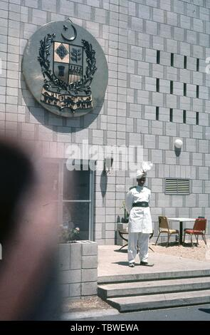 A man in uniform stands outside the Pakistan pavilion, with a coat of arms above the entrance, 1964 New York World's Fair, Flushing Meadows Park, Queens, New York, June, 1964. () - Stock Photo