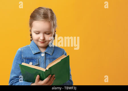 Little student girl in denim shirt on yellow background. The child is reading a book. The concept of education and school. - Stock Photo