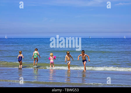 Young children on the beach, boys and girls in bathing suits / swimsuits playing in the surf and jumping over the waves at sea - Stock Photo