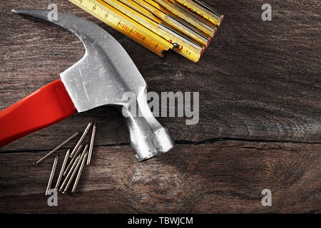 Hammer, folding rule and nails on vintage wooden table with copy space. Close up top down view. - Stock Photo