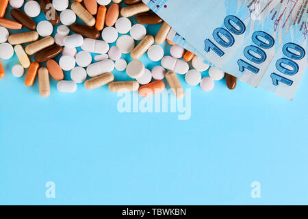 Hundred Turkish Lira bills over the medical pills. Expensive medicine and healthcare industry concept. Overhead macro view with copy space. - Stock Photo