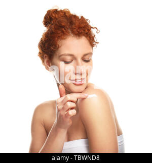 Beautiful redhead woman applying body cream against white background - Stock Photo