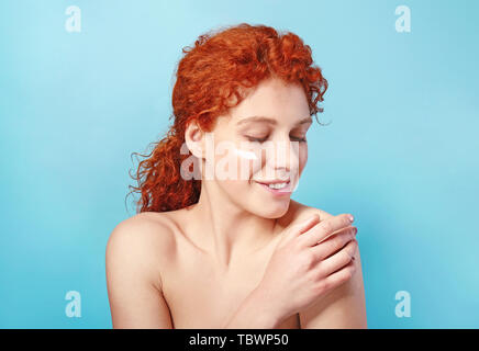 Beautiful redhead woman applying cream against color background - Stock Photo