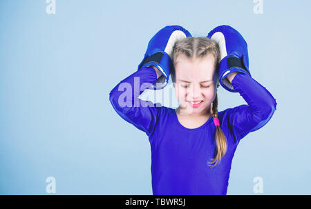 Risk of injury. Rise of women boxers. Girl cute boxer on blue background. With great power comes great responsibility. Boxer child in boxing gloves. Female boxer change attitudes within sport. - Stock Photo