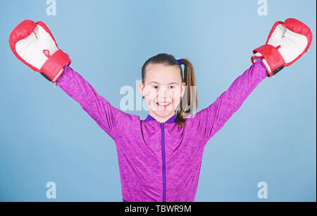 Boxing provide strict discipline. Girl cute boxer on blue background. Contrary to stereotype. Boxer child in boxing gloves. Confident teen. Enjoyment from sport. Female boxer. Sport upbringing. - Stock Photo