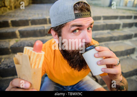 Drink something different. Caucasian hipster enjoy drinking takeaway drink with hot dog. Bearded man taking a sip of fresh coffee drink in disposable cup. Nutritional food and drink. - Stock Photo