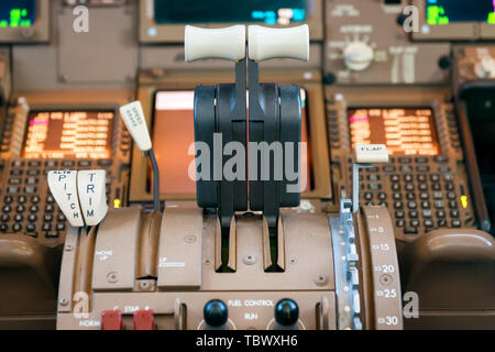 Engines thrust levers inside a big jet plane cockpit. - Stock Photo