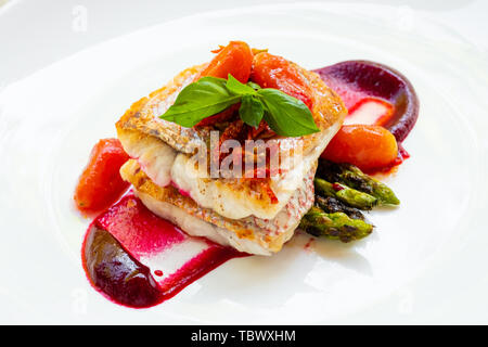 close up of a pan seared grilled red snapper fish fillet with asparagus, beetroot sauce,cherry san marzano tomatoes and basil on a white plate natural
