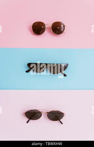 Three sunglasses on a pink and blue pastel background. The concept of summer and stylish vacation. Vertical photo. - Stock Photo
