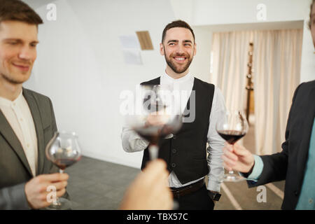 Portrait of professional sommeliers smiling happily and holding wine glasses, copy space - Stock Photo