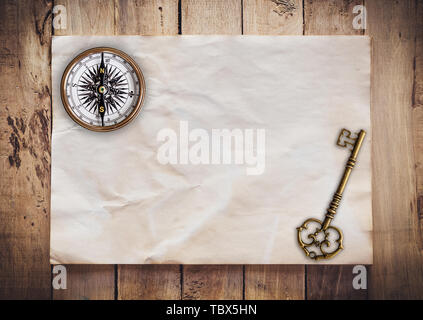 Old key and Compass on Old paper vintage on wood background with space - Stock Photo