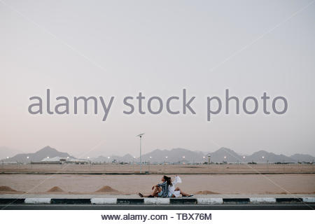 Couple of travelers resting on the road after long trip around country and enjoys amazing mountain view. Young man in checkered shirt and girl in white blouse sitting back to back and looking at sky - Stock Photo