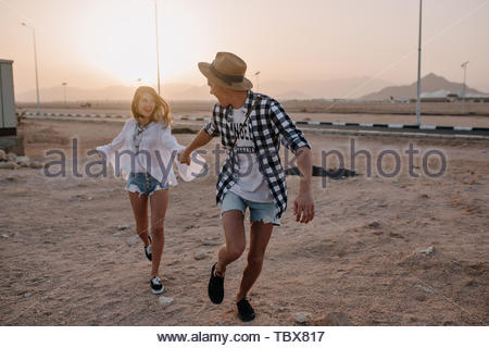 Young man in checkered shirt and denim shorts running, holding girlfriend's hand with amazing sunset behind. Charming girl in white tunic having fun and dancing with her boyfriend near the road - Stock Photo