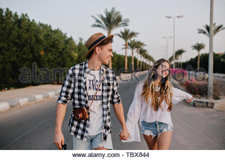 Young beautiful couple on romantic outdoor date enjoys freedom and warm summer evening in south city. Boy in trendy checkered shirt and girl in vintage white blouse walking on the road holding hands - Stock Photo