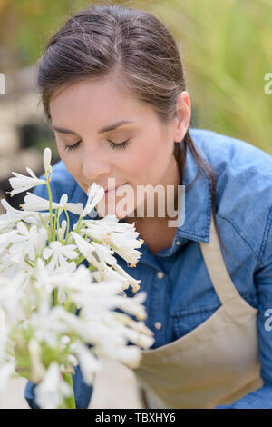 woman smelling a flower while working as a gardener - Stock Photo