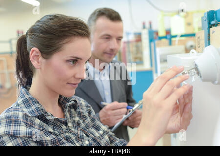 engineer showing equipment to a female apprentice close up - Stock Photo