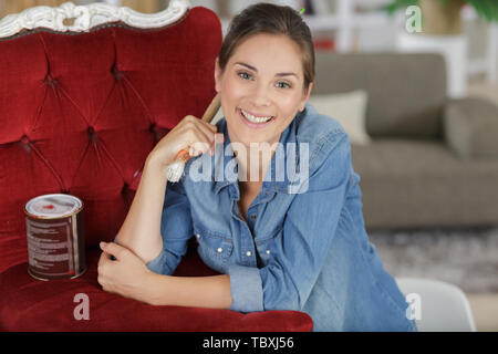 happy woman next to finished chair - Stock Photo