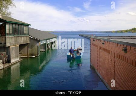 Men in a small fishing boat in Skaneateles Lake.  The pier is in the background center right - Stock Photo