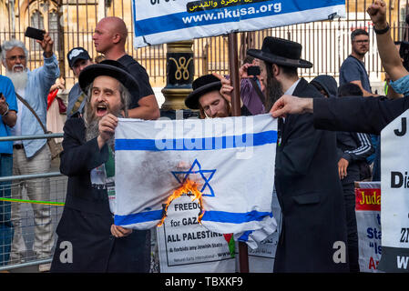London, UK. 2nd June 2019. Thousands attended the pro Palestinian Annual Al-Quds Day March organised by the Islamic Human Rights Commission. Neturei Karta Anti-Zionist Orthodox Jews burn the Israeli flag alongside the Palace of Westminster. Credit: Stephen Bell/Alamy. - Stock Photo