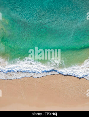 Aerial top shot of a beach with nice sand, blue turquoise water and tropical vibe of a superb tropical destination - Stock Photo