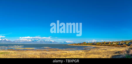 Panoramic view of a lake with snowy mountain against blue sky in the distance - Stock Photo