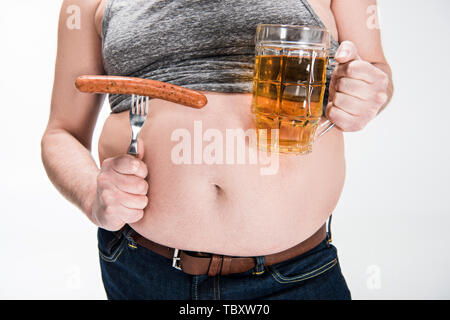 cropped view of overweight man showing belly and holding glass of beer with grilled sausage isolated on white - Stock Photo