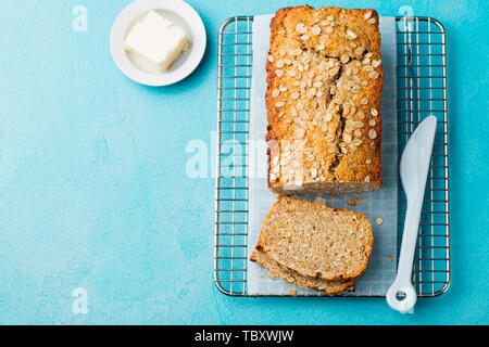 Healthy vegan oat, coconut loaf bread, cake on a cooling rack Blue background. Copy space. Top view. - Stock Photo