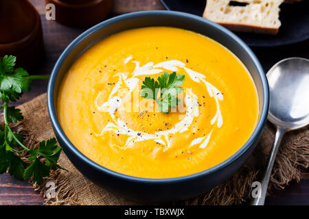 Pumpkin and carrot soup, tadka with cream and parsley on dark wooden background. Close up. - Stock Photo