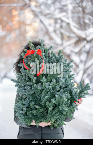Beautiful christmas tree Branches in the hands of women. Shopping at the Christmas market. Xmas mood. Preparing for the holiday. - Stock Photo