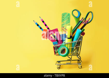 Back to school concept with shopping cart and colorful pencils, square ruler, scissors, clips, markers on pastel yellow backdrop.