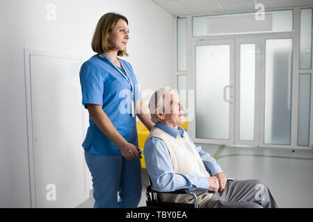 Thoughtful nurse pushing senior patient in wheelchair at hospital - Stock Photo